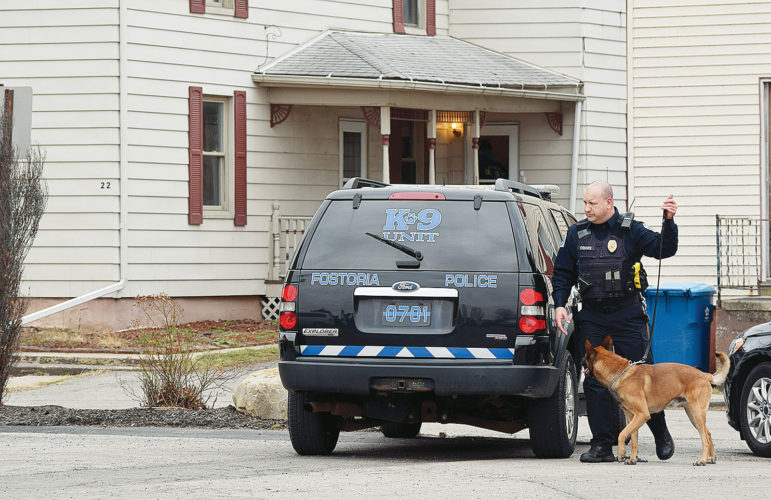 PHOTO BY JILL GOSCHE Officer Don Dennis and K9 Marley of Fostoria Police Department work at the scene of a search warrant at 22 Tiffin St., Tiffin, Monday.