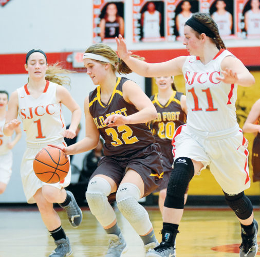 PHOTO BY JILL GOSCHE  Old Fort's Jordan Magers controls the ball against the defense of St. Joe's Ava Stepanic (left) and Callie Kelbley during the game in Fostoria Thursday.