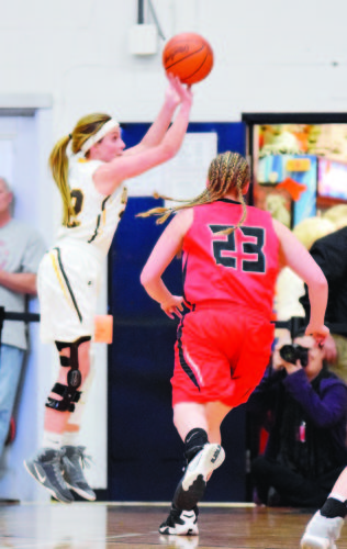 PHOTO BY JILL GOSCHE  Old Fort's Peyton Miller shoots and scores as Hicksville's Ashley Peter defends during the regional semifinal game at Elida Thursday.