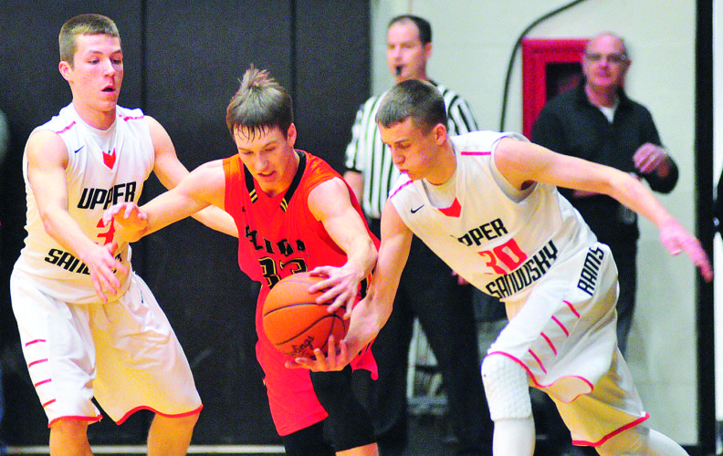 PHOTO BY PAT GAIETTO Upper Sandusky's Harrison Sheaffer (left) and Ry Adams pressure Elida's Daniel Unruh during the Division II district final at Ada Saturday.