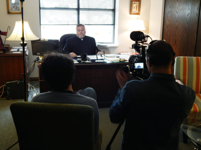 PHOTO BY MARYANN KROMER Max Kern (left) and Philipp Majer (right) prepare to record an interview with the Rev. Todd Dominique Monday at St. Wendelin Parish.