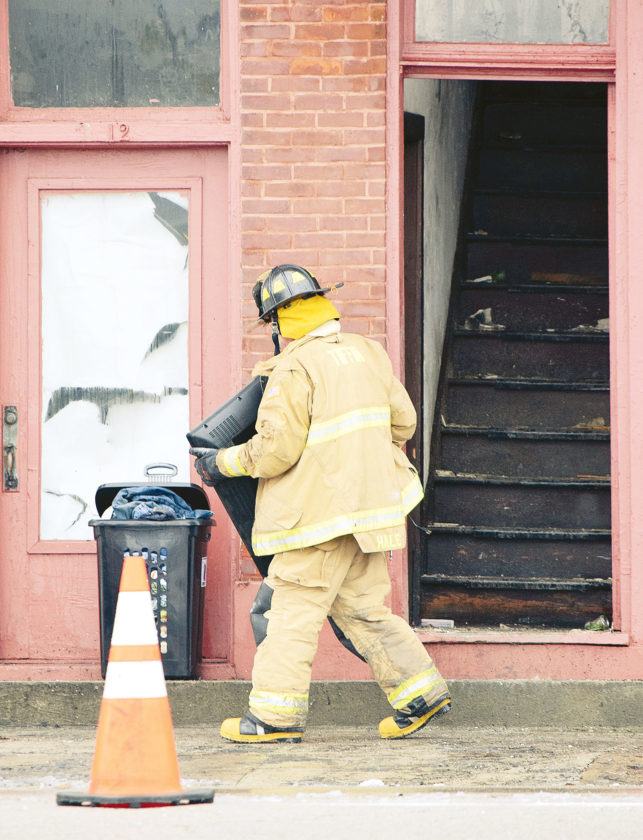 PHOTO BY JILL GOSCHE Tiffin Fire Rescue Division's Joel Hale carries a television from the East Market Street building that burned Friday.