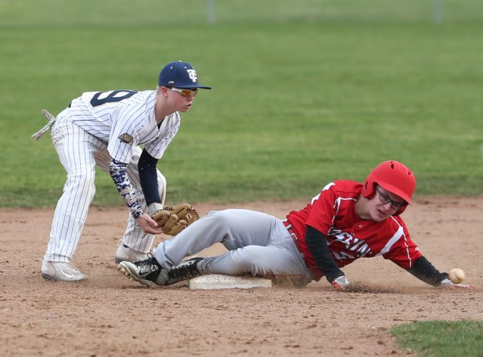 PHOTO BY STEVE WILLIAMS TC's Quinton Smith (left) waits to receive a throw from catcher Matt Boes as a Port Clinton player slides in safely ahead of the ball Wednesday in Tiffin.