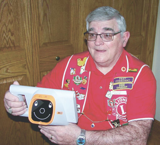 PHOTO SUBMITTED Dwight Everhart, Attica Lions Club sight chairman, tests out the equipment used in the Lions' early children's eyesight testing program.