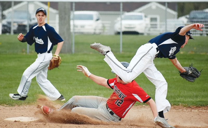 PHOTO BY JILL GOSCHE Mohawk's Tanner Osborn steals second base as Carey's Easton Roark (right) attempts to get the out and Reece Mullholand provides backup during the game in Carey Monday.