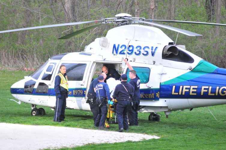 PHOTO BY PAT GAIETTO Tiffin Fire Rescue Division personnel help load a person into a Life Flight helicopter at Hedges-Boyer Park Thursday evening.