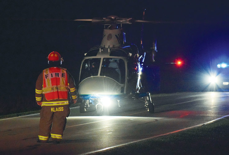 PHOTO BY JILL GOSCHE Capt. Mike Klaiss of Bettsville Volunteer Fire Department watches as Life Flight prepares to leave the scene on CR 31 early Saturday morning.