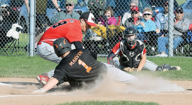PHOTO BY JILL GOSCHE Seneca East's Ryan Marvin safely slides into home as Mohawk's Rico Lopez (left) and Parker Brown try to get him out during the game in Attica Monday evening.