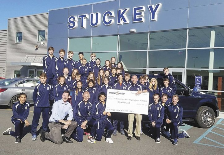 "Courtesy photo Matt Stuckey (light blue shirt), president of Stuckey Ford, Hollidaysburg, and his team recently hosted Ford's ""Drive One for Your School"" fundraiser to benefit the Hollidaysburg Area Senior High School's Golden Tigers' cross-country team. More than 200 participants test drove a Ford vehicle in exchange for a $25 donation. The campaign raised $6,000 to fund new warm-up suits for the entire team."