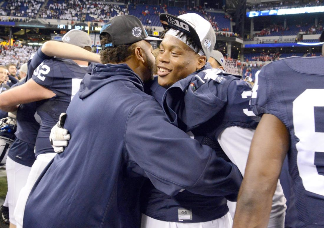Mirror photo by Patrick Waksmunski / Penn State defensive tackle Kevin Givens receives a congratulatory hug after the Lions beat the Wisconsin Badgers in the Big Ten championship game at Lucas Oil Stadium in Indianapolis, Ind., on Saturday evening. The Nittany Lions pulled off a  remarkable comeback late Saturday night to beat Wisconsin, 38-31.