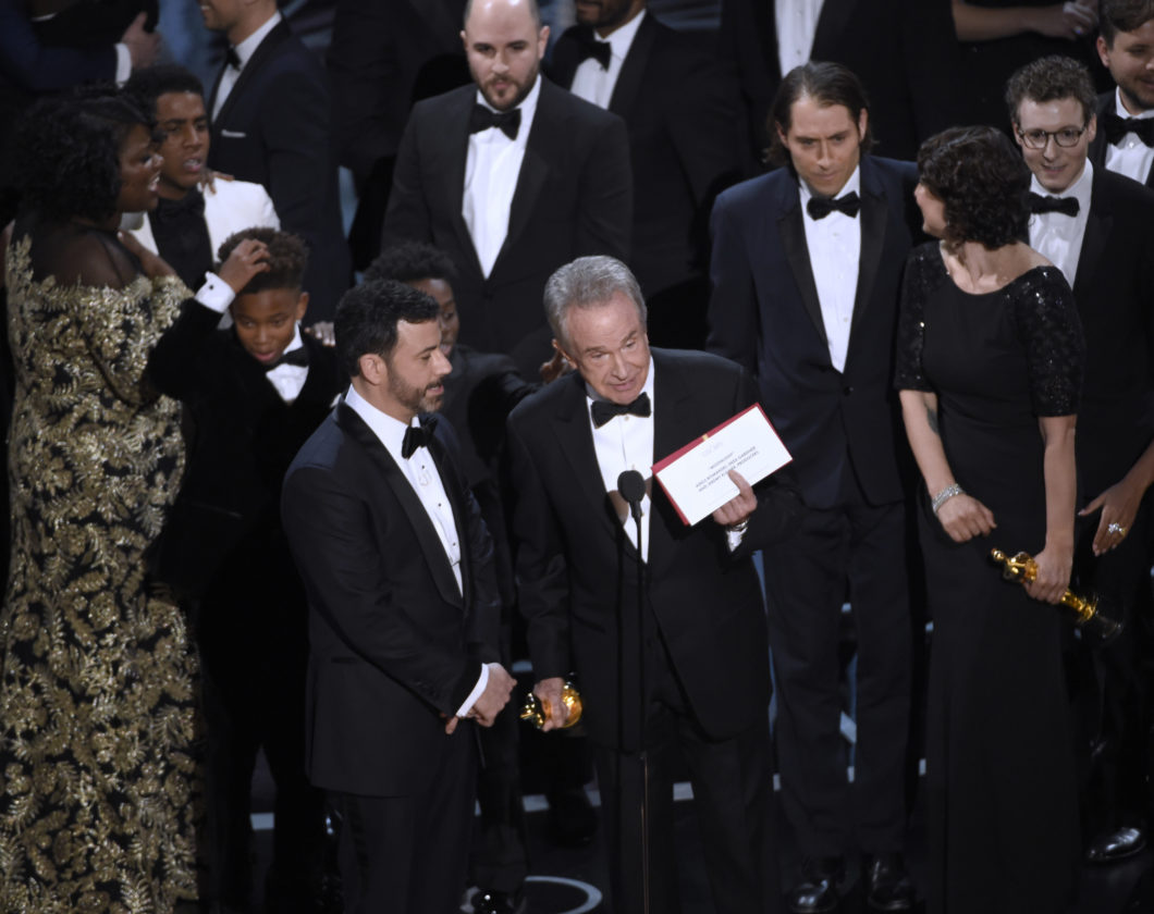 take two at the oscars moonlight wins best picture after mix up presenter warren beatty shows the envelope the actual winner for best picture as host jimmy kimmel left looks on at the oscars on sunday feb