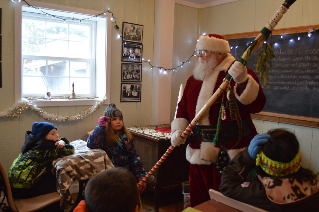 Haley Gustafson | Daily Press  Santa Claus tells the history of his walking stick to a group of Lemmer Elementary students in the schoolhouse located at the Antique Village at the U.P. State Fairgrounds Friday afternoon. Santa visited the village during the U.P. Steam and Gas Engine Association's Christmas in the Village Friday and Saturday.