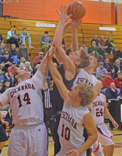 Mike Mattson | Daily Press Negaunee's Trent Bell gets sandwiched by Escanaba defenders Dalton Deneau (14), C.J. Barron (10) and Tyler Willette while battling for a rebound in Tuesday's season-opener. The 6-foot-7 Bell produced a career-high 37 points and 16 rebounds in the Miners' 68-48 season-opening win against the Eskymos.