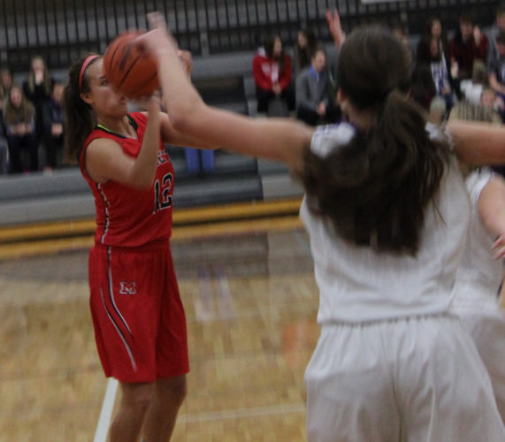 Avery Bundgaard | Daily Press Marquette's Amber Manitowabi Huebner pulls up for a three point shot Tuesday night against Gladstone. Marquette won the game 60-32.