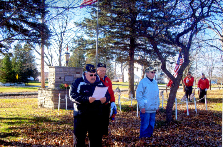 "Courtesy photo The Floriano-Stecker-Kelly Auxillary held their Veterans Day program on Nov. 11 in Hermansville. Pictured, left, Commander James Wash giving the opening speech at the ceramony, Walter Bellmore, Sergant-at-Arms, and Jane Peters, Chaplain, in front of the marker that was erected in October 1972 by the local American Legion Post. The marker reads ""Dedicated to the Men and Woman who served our country in war and peace."" The Veterans Day dinner followed that night, which goes back to 1953 when it was first organized."