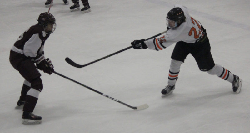 Dennis Grall | Daily Press Colton Hayes of Escanaba follows through on his shot that blinked the red light for a first-period goal against University of Detroit Jesuit Sunday in Wells. Defending is Michael Coletti.