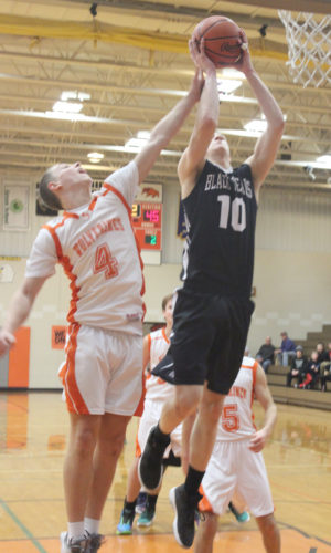 Dennis Grall | Daily Press Tyler Johnson (10) of Big Bay de Noc soars above Mid Peninsula's Terry Brower to grab possession of a rebound Monday, then he followed by tipping it into the basket in the fourth quarter to bring the Black Bears within 49-47. Mid Pen won 57-51.
