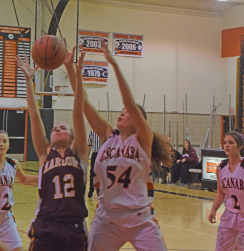 Mike Mattson | Daily Press Menominee's Corrina Anderson (12) and Escanaba's Jen Brandt (54) go after a loose ball in Monday night's game. Esky outrebounded the Maroons 41-28 en route to a 61-41 victory.