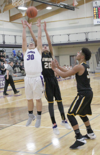 Avery Bundgaard | Daily Press Gladstone's Owen Hanson (30) and Gwinn's Isaiah Guevara (20) scramble for a rebound Tuesday at Gladstone.