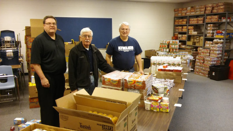 Courtesy photo Pictured setting up tables to fill backpacks are Mike Macfarlane, Mike Albrecht, and Larry Kirschner. Backpacks are filled aand delivered every Thursday night for kids can pickup them up Friday for the weekend.