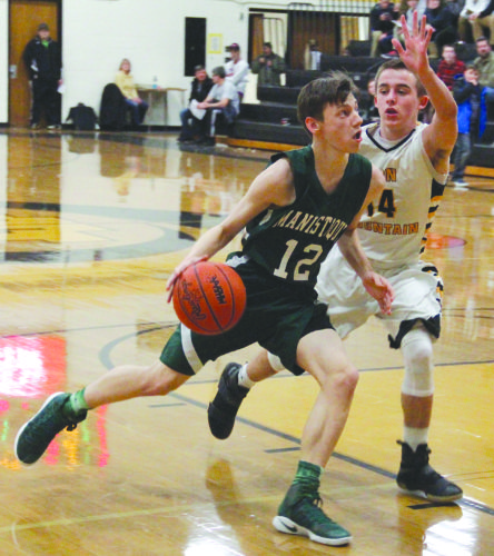 Adam Niemi/Iron Mountain Daily News Manistique senior Colton Hoholik drives to the basket as Iron Mountain freshman Marcus Johnson defends on Thursday in Iron Mountain.
