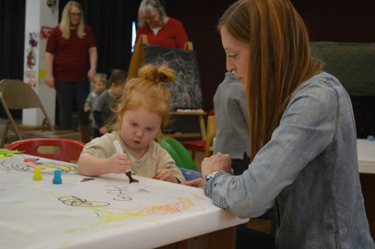 Haley Gustafson | Daily Press Clara Pfotenhauer, 2, creates a picture while her mother Stephanie watches Thursday afternoon during the Bonifas Art Center's Toddler Art class.