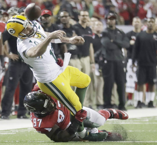 Green Bay Packers' Aaron Rodgers throws while in the grasp of Atlanta Falcons' Grady Jarrett during the second half of the NFL football NFC championship game, Sunday, Jan. 22, 2017, in Atlanta. (AP Photo/David Goldman)