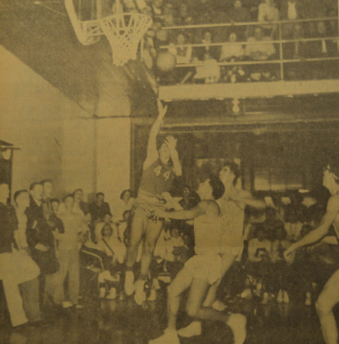 Daily Press photo Gladstone basketball player Jim LaLonde goes up for a jump shot as Eskymos center Jim Anderson attempts to block the ball in this 1957 sport photo. The Braves went on to defeat the Eskymos during the Great Lakes Conference game with a score of 56-54.