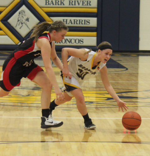 Dennis Grall | Daily Press Kelsey Boucher of Bark River-Harris dribbles atop the key to get around Forest Park defender Abby Nylund Thursday at Harris. BR-H stunned the top-ranked Trojans 73-60.