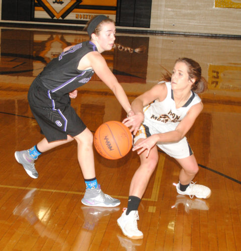 Burt Angeli/The Daily News Gladstone's Kaitlyn Hardwick defends Iron Mountain's Brianna Hoffman in Thursday's game.