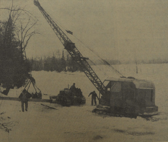 Daily Press photo  An ice covered Ford River trapped a large tractor of the Denison Construction Co., out of Munising in 1957. The ice gave way and the heavy equipment settled to the bottom in about four feet of water. At the time, the contractor was at work on the new 120-foot bridge spanning Ford River, which is one and a half miles north of Hyde. The bridge was finished the following spring and the total cost of the project was $60,000.