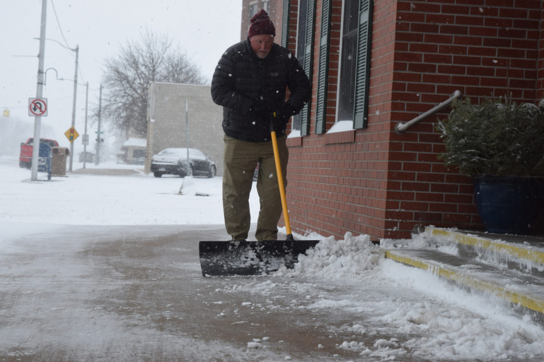 Haley Gustafson | Daily Press Paul Fix shovels outside of Northern Insurance Agency in Escanaba Friday morning. Winter weather made a comeback after a week of warm temperatures. According to the National Weather Service, more snow is expected in Escanaba this weekend, with a 50 percent chance of snow on Saturday, mainly before 1 p.m., and a 40 ­percent chance of snow showers during the day on ­Sunday. Both days could see blowing snow, with gusting winds reaching speeds of 25 miles per hour.