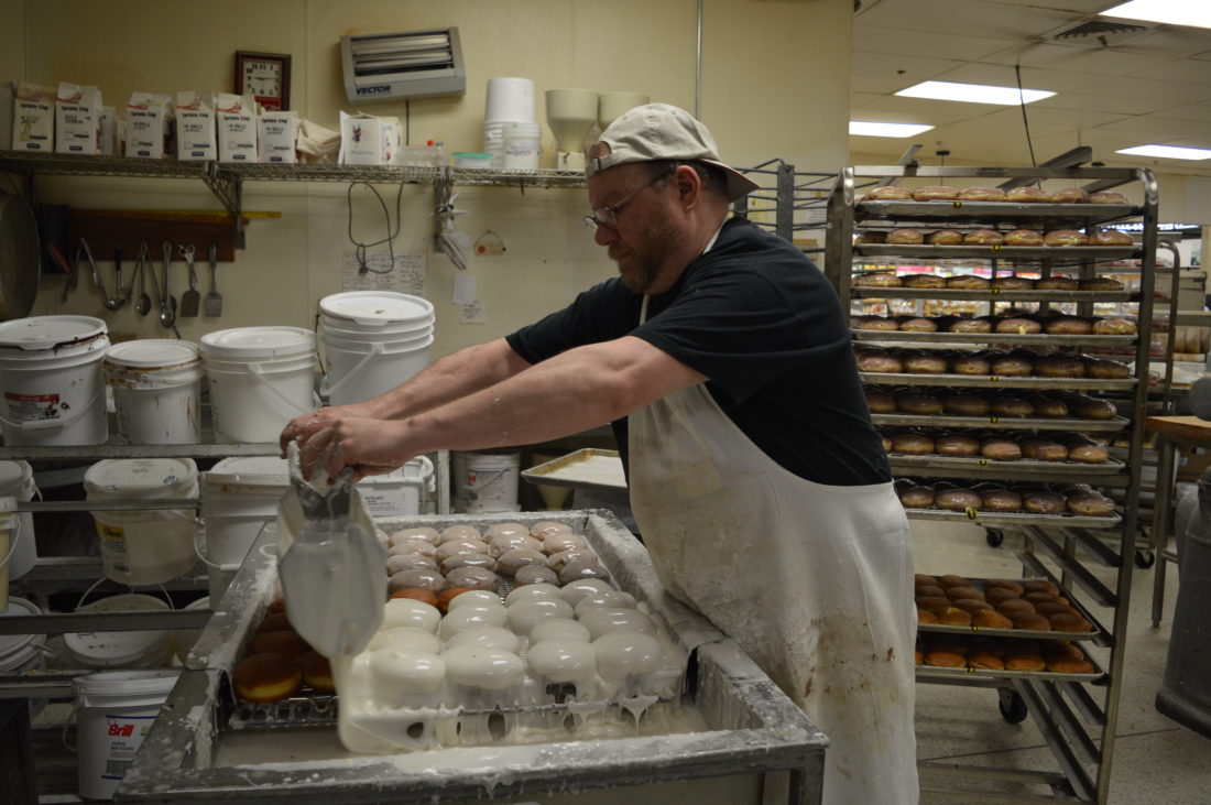Jordan Beck | Daily Press Doug Eubank, a bakery employee for Elmer's County Market, glazes a tray of paczkis Monday. According to Art Ziebell, the bakery's manager, raspberry is the most popular flavor of paczkis at Elmer's.