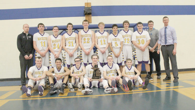 Avery Bundgaard | Daily Press The Rapid River Rockets pose with the trophy after beating Mid Peninsula 60-50 Wednesday night for the Class D district title.