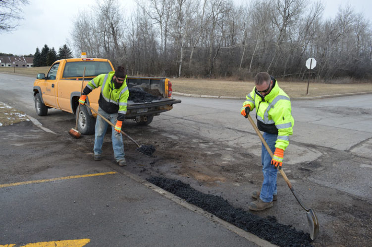 Jordan Beck | Daily Press Escanaba Department of Public Works employees Adam Fix, right, and Tim Hoffmeyer patch a pothole near the Delta-Schoolcraft Intermediate School District building on 3rd Avenue South and South 26th Street in Escanaba Monday. Escanaba City Engineer and Director of Public Works Bill Farrell said inconsistent temperatures seen in the area recently have made the pothole situation worse.