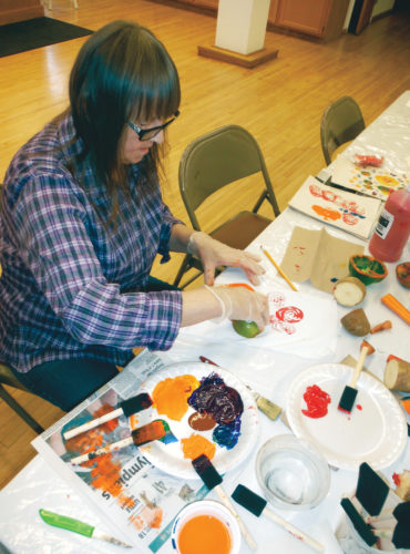 Jenny Lancour | Daily Press Hilma Lehtonen, of Escanaba, hand stamps painted fruits and vegetables on paper as she practices to create an apron into wearable art during senior art classes at the Bonifas Arts Center in Escanaba on Tuesday. Upcoming classes — including abstract painting, ceramics and jewelry — are free to senior citizens from 1 to 3 p.m. on March 28, April 11, April 25, May 9, May 23, June 6, and June 20. Contact the arts center at (906) 786-3833 for more information.