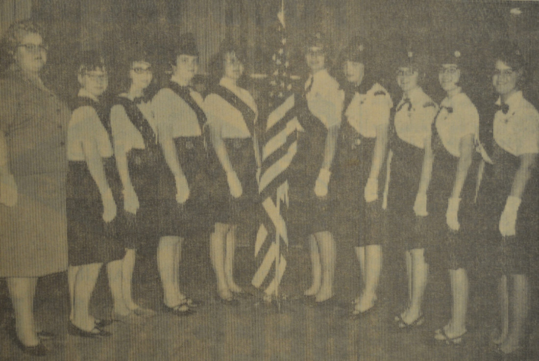"""Daily Press photo Cadettes from Troops 2 and 4 of Escanaba were received into Senior Girl Scout Troop 24 in a traditional capping ceremony at the V.F.W Hall in this 1966 photograph. The program included an opening flag ceremony and a """"dramatic skit."""" Pictured from left are: Mrs. Clifford Mineau, Barbara Schmit, Laurel Weiland, Joan McDonnell, Gladys Williams, Maureen Richards, Ann Schmidt, Diane Rose, Pat McMonagle, and Katie Prininski."""