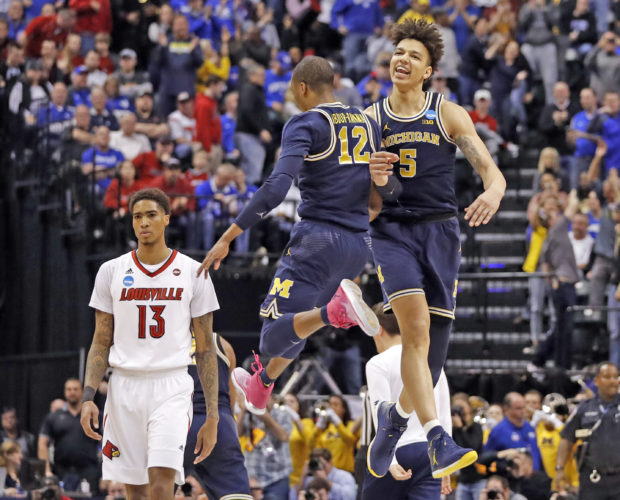 AP photo Michigan's D.J. Wilson (5) and teammate Muhammad-Ali Abdur-Rahkman (12) celebrate as Louisville's Ray Spalding (13) walks past following the Wolverine's 73-69 upset win Sunday in Indianapolis.