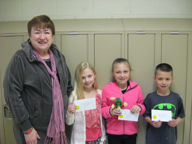 """Courtesy photo The National Association for Family and Community Education (FCE) recently held their 2017 Character Counts Essay and Artwork Contest. Students in the 4th grade were invited to participate by writing an essay and developing a poster depicting """"CARING.""""  Cindy Brock, chairperson of the Character Counts contest and member of the Town 'n' Country Study Group congratulates Hailey Paquette, third place winner; Emma Sundling, first place winner; and Adam Frappier, second place winner. All students are from Sandy Sauve's fourth grade class at Rapid River School. Cash awards were presented as well. Emma is holding """"Clarence, the Caring Alligator,"""" the stuffed mascot. Emma Sundlings' first place entry goes on to the state competition in April, and from there, Michigan sends their first place winner to the national competition."""