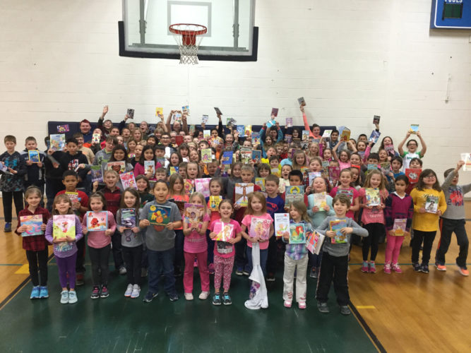 "Courtesy photo Bark River Harris Elementary students in grades K-6 show off the books they won during Book Bingo, an activity taking place at the school in conjunction with March Reading Month. During the month, the theme of ""Reading through the Decades"" is being celebrated along with book bingo, and a black out event where students will go without using any form of technology for one day. For the cumulation of the month, students will be treated to ice cream sundaes, supplied by the Bark River Harris PTO."