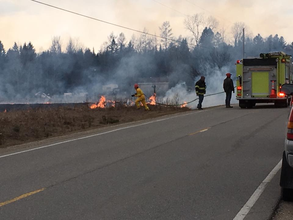 Courtesy photo Escanaba Township firefighters battle a grass fire earlier this month. Spring is a busy time for area firefighters as the risk of wildfires increases dramatically.