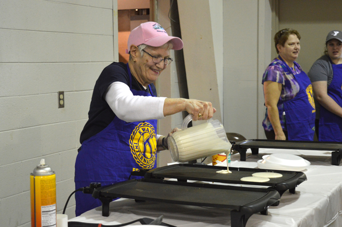 """Haley Gustafson   Daily Press  Escanaba Kiwanis Member Dorothy Kollman is all smiles as she makes pancakes Friday evening during the Escanaba Kiwanis Home and Garden Show/Pancake Days. The show, which continues today and Sunday, features Michigan State Extension (MSUE) """"Smart Gardening"""" sessions, pancake meals, over 60 vendors for home owners/gardeners and more. Although there is no admission charge for the show, the cost of the pancake meal that includes scrambled eggs and sausage is $6 for adults, $4 for children ages 6-12. Kids under six eat free."""