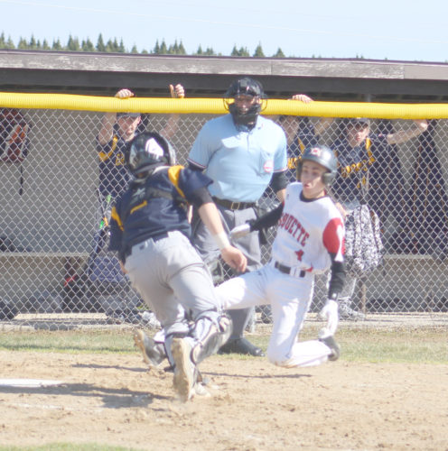 Avery Bundgaard | Daily Press Marquette's Alec Beauchamp slides into home plate trying to beat the tag from Bark River-Harris catcher Logan Heim Thursday at Bark River. Beauchamp was called out on the play.
