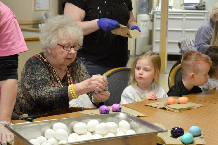 Haley Gustafson   Daily Press Christian Park Healthcare resident Genieve Smoot colors an Easter egg while Country Schoolhouse student Emily Lockwood looks on Friday at Christian Park Healthcare in Escanaba. The residents and students colored about 120 eggs to be distributed throughout the facility for the upcoming Easter holiday on Sunday.
