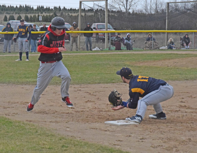 Mike Mattson | Daily Press North Central's Carter Holle attempts to reach first base as Bark River-Harris first baseman Ray Cole awaits a low throw. Holle was running after a dropped third strike and was out on the play. The teams split Tuesday's doubleheader.