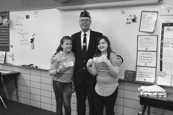 "Haley Gustafson | Daily Press  At center, William Porath, commander of the Delta County Disabled Veterans of America (DAV), poses with  the  two  essay  winners from Jones Elementary School in Gladstone, Rainah Beauvias, left, and Tacey Weber, right. The girls won an essay contest put on by the DAV with the topic ""What Memorial Day means to Me."" Beauvias took first place and was awarded $50, and Weber placed second and was given $25. In addition, the winning student's essays will be sent downstate for further review and possibly more awards for the contest."