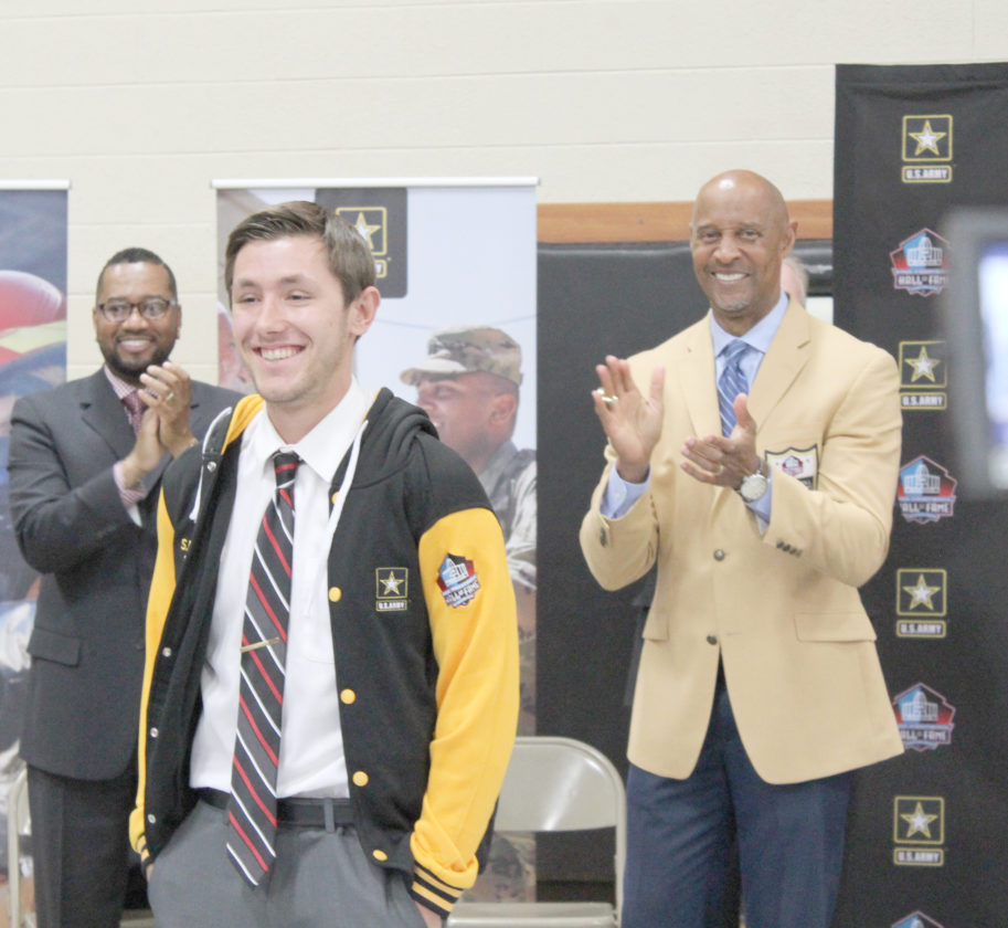 Avery Bundgaard | Daily Press Seth Polfus is honored as a finalist for the Award for Excellence on Wednesday at North Central High School. Pro Football Hall of Famer James Lofton, right, presented Polfus with the honor.