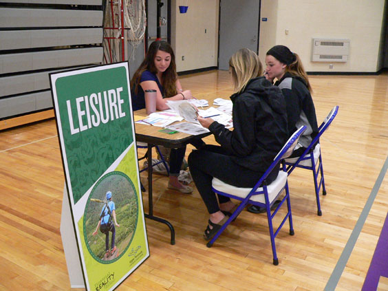 "Haley Gustafson | Daily Press  Great Lakes First Federal Credit Union representative Vanessa Peterson discusses leisure costs with Gladstone High School juniors Jayci Cole, left, and Taylor Hunter, at far right, during the Financial Reality Fair held at the school Tuesday. At the fair, students learned the importance of fiscal responsibility from various credit unions in the area. Students were given budgets to spend ""money"" on various life scenarios such as career, housing, food expenses, transportation costs, and many others."