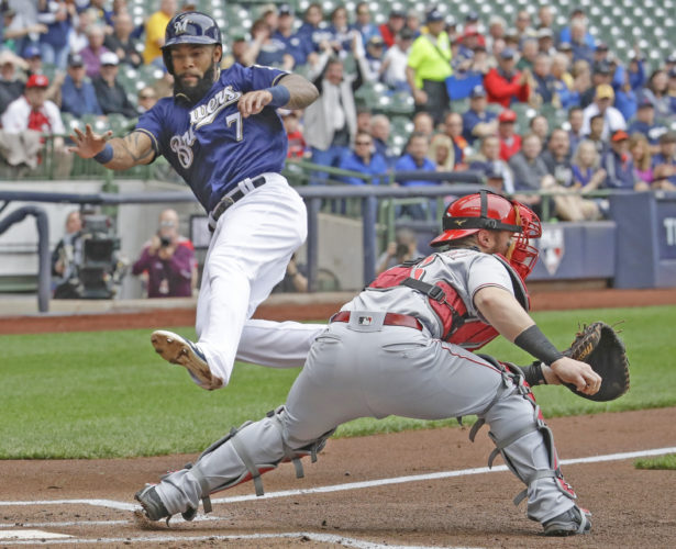 AP photo Milwaukee's Eric Thames scores past Cincinnati Reds catcher Tucker Barnhart during the first inning Wednesday in Milwaukee. Thames, who left the game later with an apparent hamstring injury, scored from first on a double by Ryan Braun.