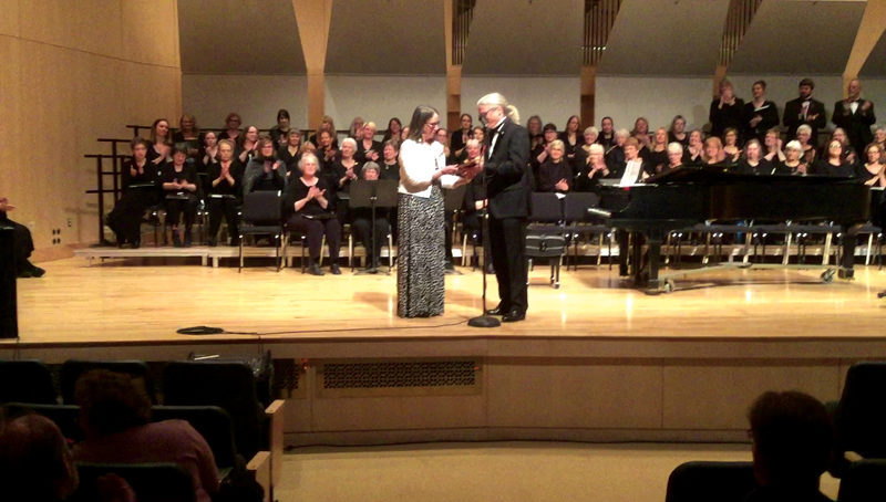 Courtesy Photo  Local choir director and vocal teacher Ann Wood, left, receives the Upper Peninsula Choral Leadership Award from Marquette Choral Society President Bruce Larson at a concert in Marquette last Sunday.